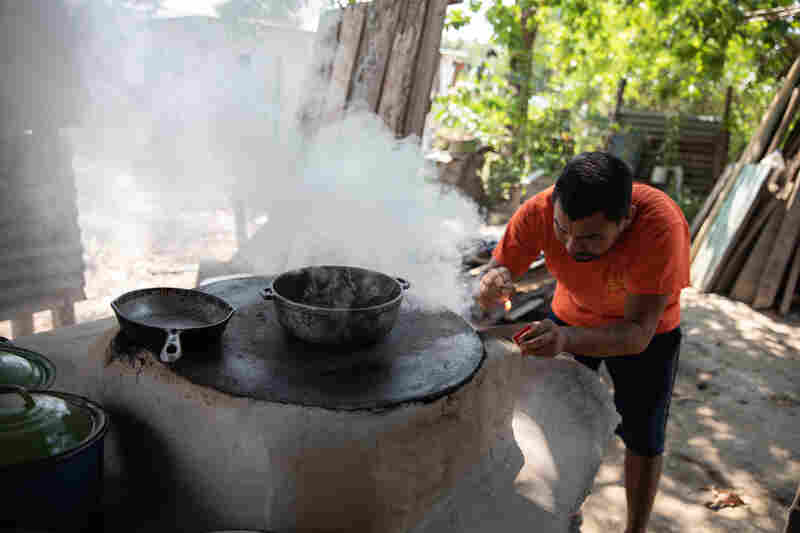 Adan Ramos lights the wood fired oven his wife, Blanca, uses to make tortillas, the family's only source of income after the 2020 hurricanes destroyed their home and neighborhood.